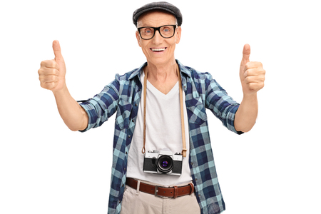 posing  agree: Joyful senior tourist giving two thumbs up isolated on white background