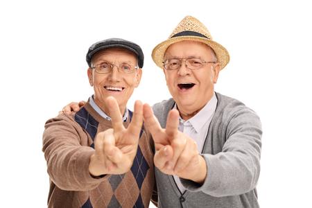 Due signori anziani gioiosi facendo segno di pace con le mani isolato su sfondo bianco