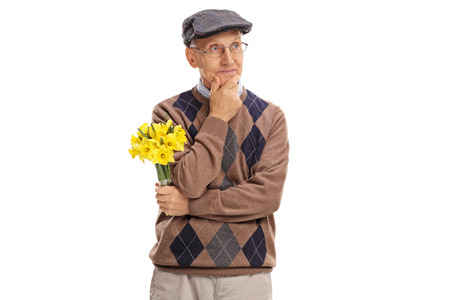 stood up: Pensive senior gentleman holding a bunch of flowers and looking in the distance isolated on white background