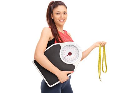 woman on scale: Young girl holding a weight scale and a measuring tape isolated on white background