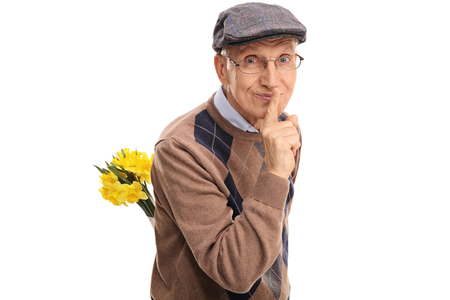 old man: Romantic senior holding a bunch of flowers behind his back and gesturing silence isolated on white background Stock Photo