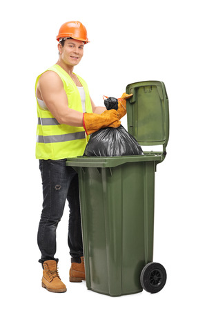 emptying: Full length portrait of a young male waste collector emptying a garbage bin isolated on white background