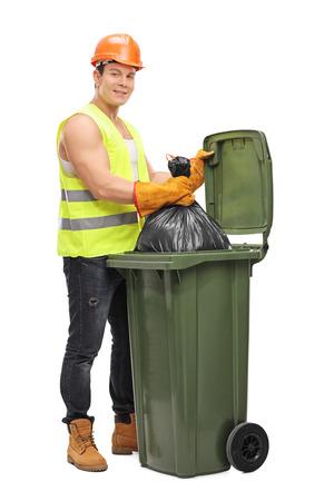 recolector de basura: Retrato de cuerpo entero de un joven recolector masculina vaciar un cubo de basura aislado en el fondo blanco