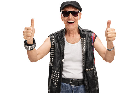 posing  agree: Studio shot of a senior punk rocker giving two thumbs up isolated on white background