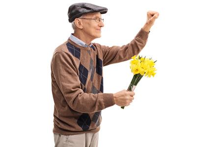 tocar la puerta: Mayor que sostiene flores y se prepara para llamar a una puerta aislada en el fondo blanco Foto de archivo