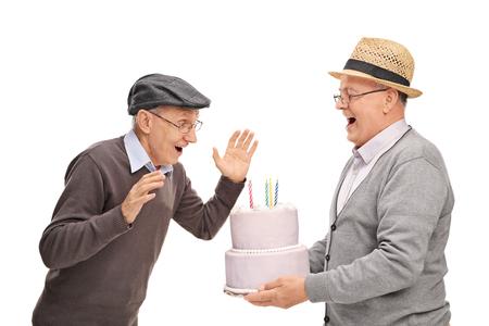 elderly man: Joyful senior bringing birthday cake to his surprised friend isolated on white background