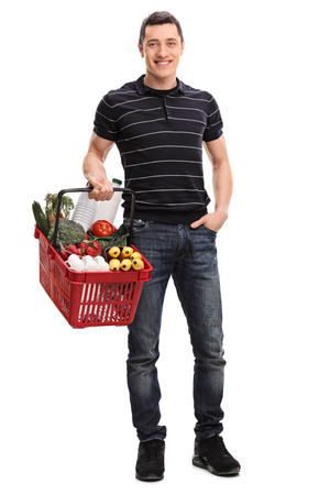 food shop: Full length portrait of a young man holding a shopping basket full of groceries isolated on white background Stock Photo