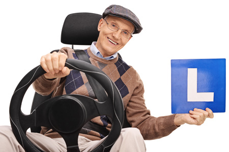 gentleman: Cheerful senior gentleman holding an L-sign seated on a car seat isolated on white background Stock Photo