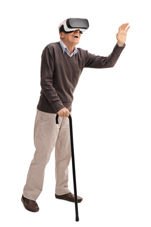 experiencing: Full length portrait of a senior with a cane experiencing virtual reality through VR headset isolated on white background