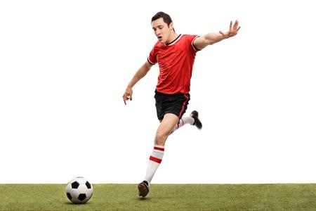 hombre disparando: Tiro joven jugador de fútbol en el momento justo antes de dar patadas a un balón aislado en el fondo blanco