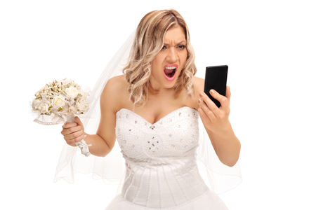 screaming: Furious young bride looking at her cell phone and screaming isolated on white background