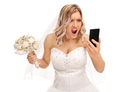 joven novia furiosa que mira su teléfono celular y gritando aislados sobre fondo blanco