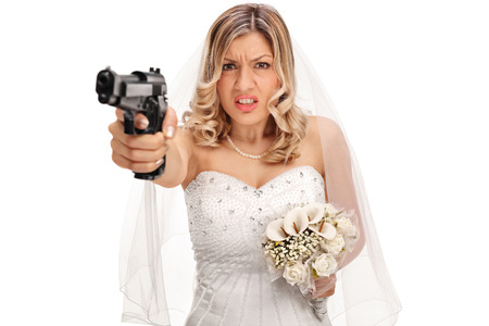 mislead: Desperate young bride pointing a gun towards the camera isolated on white background