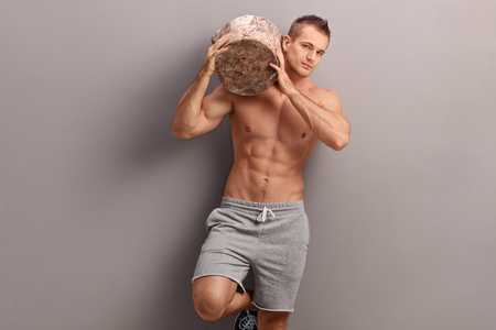 shoulder carrying: Handsome muscular guy carrying a huge log on his shoulder and looking at the camera