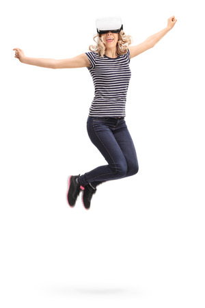 midair: Vertical shot of a young joyful woman experiencing virtual reality and jumping shot in mid-air isolated on white background