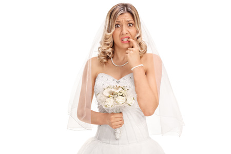 Nervous young bride biting her nails and looking at the camera isolated on white background Фото со стока
