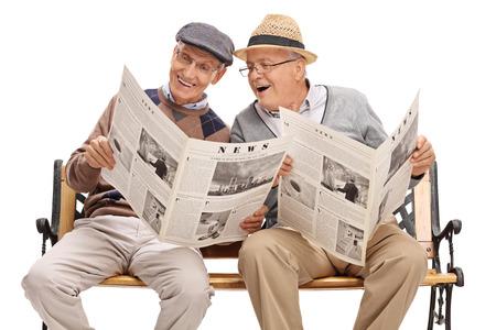 Mayor que muestra algo en el periódico a su amigo sentado en un banco aislado en el fondo blanco