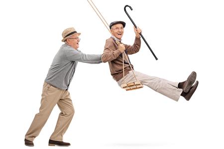Twee vrolijke senior heren swingende op een schommel en plezier op een witte achtergrond Stockfoto