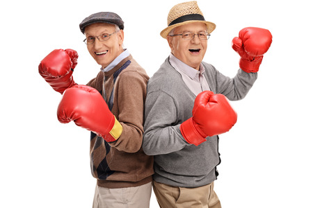posing: Two senior gentlemen posing together with boxing gloves isolated on white background