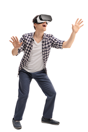 experiencing: Full length portrait of  young excited man experiencing virtual reality isolated on white background Stock Photo