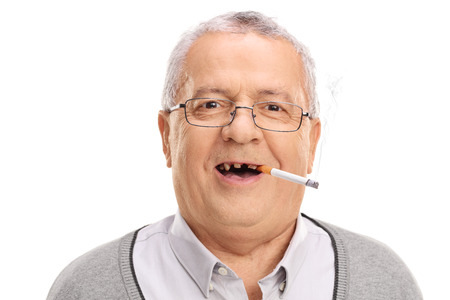 senior smoking: Portrait of a toothless senior smoking a cigarette and looking at the camera isolated on white background