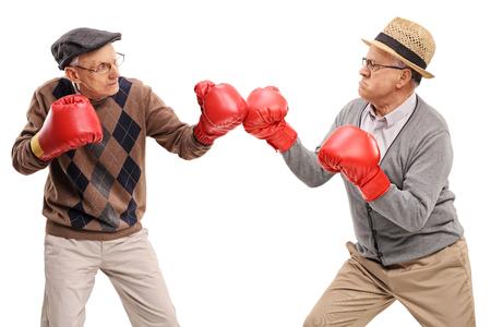 enfado: Estudio tirado de dos personas mayores competitivos que luchan entre sí con guantes de boxeo aislado en el fondo blanco