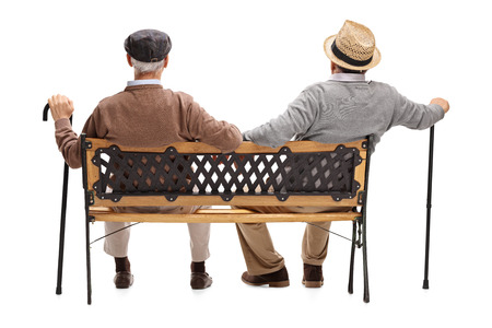 白い背景に分離された木製のベンチに座っている二人のリラックスした上級紳士の背面ビュー スタジオ撮影