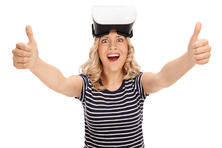posing  agree: Satisfied young woman giving two thumbs up after using a VR headset isolated on white background Stock Photo