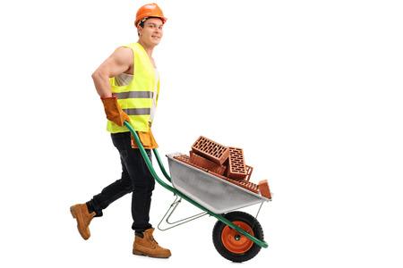 empujando: trabajador de la construcción que empuja una carretilla con una carga de ladrillos en ella y mirando a la cámara aislada en el fondo blanco
