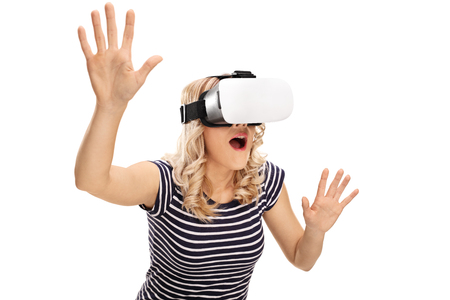 experiencing: Young amazed woman experiencing virtual reality isolated on white background