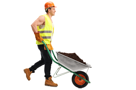 dirt pile: Construction worker pushing a wheelbarrow with a pile of dirt in it isolated on white background