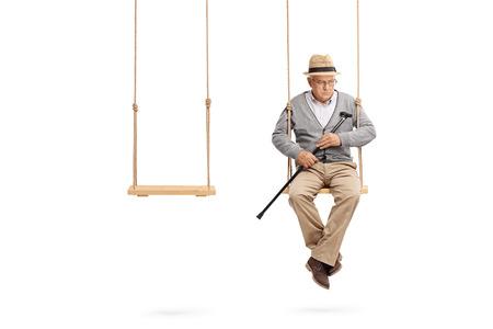 Eenzame senior zittend op een houten schommel met een lege swing naast hem op een witte achtergrond