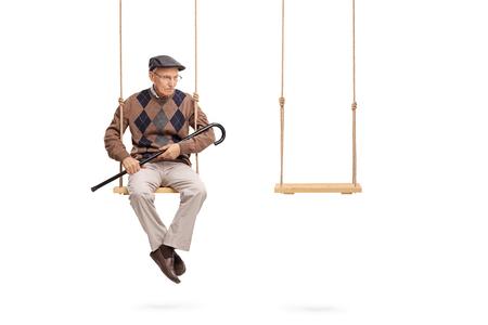Studio shot van een trieste senior zittend op een schommel met een lege swing naast hem op een witte achtergrond