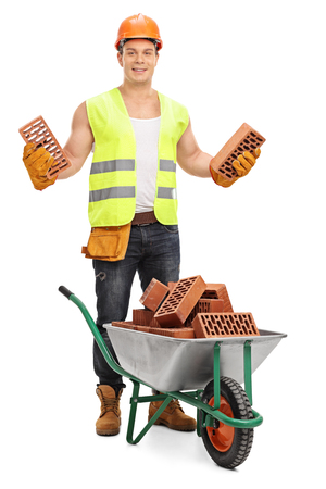 Construction worker holding bricks behind a wheelbarrow isolated on white background
