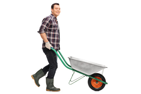 wheelbarrow: Young gardener pushing a wheelbarrow and looking at the camera isolated on white background