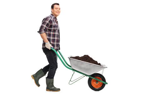 Full length portrait of a young gardener pushing a wheelbarrow full of dirt isolated on white background