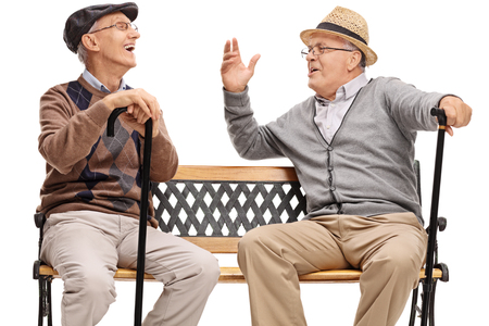 Two retired elderly people sitting on a bench and laughing isolated on white background Stock Photo