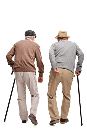 rear view: Two elderly people walking with canes isolated on white background, rear view