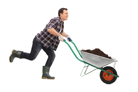 Young gardener pushing a wheelbarrow full of dirt and running isolated on white background Stock Photo