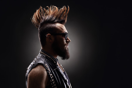 Profile shot of a young punk rocker with a Mohawk hairstyle on dark background Stock Photo