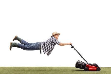 흰색 배경에 고립 된 강력한 잔디 깎는 기계에 의해 끌려 가고있는 성숙한 남자의 스튜디오 샷