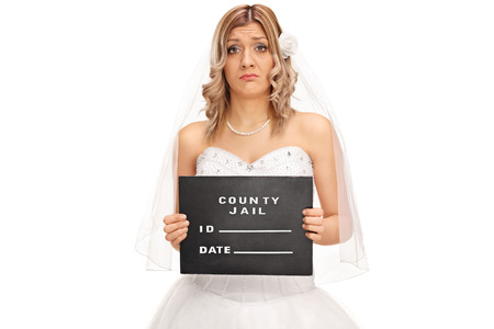 arrest women: Studio shot of a sad young bride posing for a mug shot isolated on white background