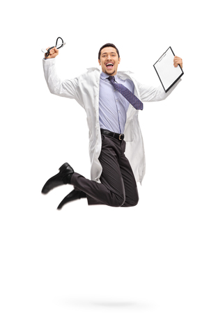 midair: Vertical shot of an overjoyed doctor holding a clipboard and jumping out of joy shot in mid-air isolated on white background