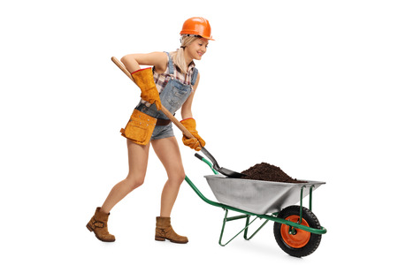 shovel in dirt: Female construction worker unloading a wheelbarrow full of dirt with a shovel isolated on white background Stock Photo