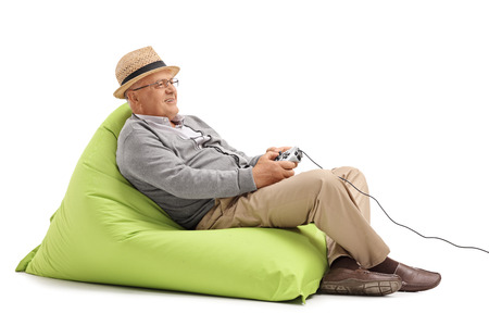 gamer: Relaxed mature man sitting on a green beanbag and playing video games with a gamepad isolated on white background