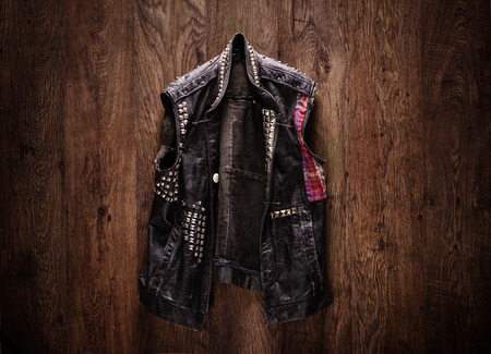 safety jacket: Old-school punk-rock leather jacket hanging on a wooden background