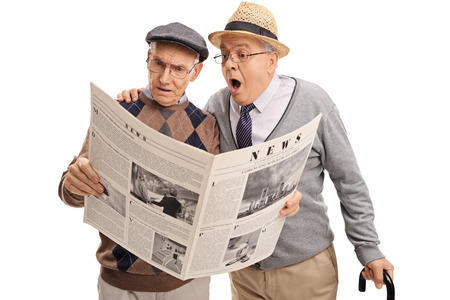 person reading: Two baffled senior gentlemen reading a newspaper isolated on white background