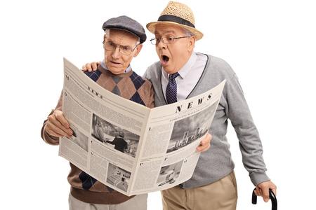baffled: Two baffled senior gentlemen reading a newspaper isolated on white background