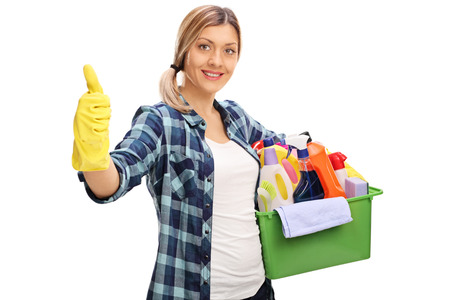 posing  agree: Cheerful girl holding a bunch of cleaning products and giving a thumb up isolated on white background