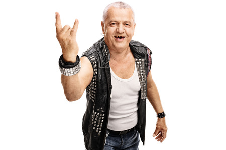 hardcore: Senior punker in a black leather jacket with pins making a hardcore hand gesture isolated on white background Stock Photo